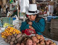 Peru, Cusco, San Pedro Market.  Peruvian Woman Selling Two  Varieties of Potatoes, plus Olluco (far left, orange-colored), an Andean vegetable.