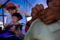 Rian teaches Kartini Emergency School's seventh grade students, 13 year old Lanjar Arum Sari (left) and her sister 14 year old Siti Rahayu, needlework during a class on practical skills at the new temporary location of Kartini Emergency School at a makeshift tent set up on an empty lot in North Jakarta. Since the early 1990s, twin sisters Sri Rosyati (known as Rossy) and Sri Irianingsih (known as Rian) have used their family inheritance to set up and run 64 schools in different parts of Indonesia, providing primary education combined with practical skills to some of the country's most deprived children.