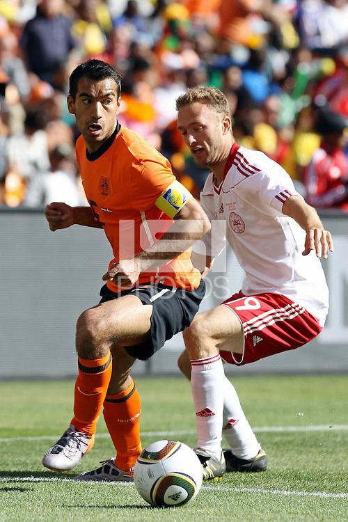 Giovanni van Bronckhorst of Holland and Dennis Rommedahl of Denmark battle for the ball