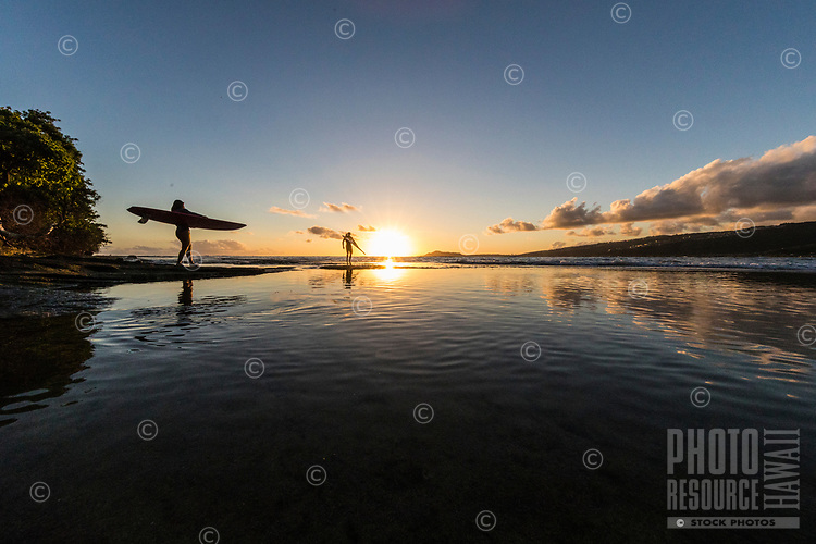 A couple going out for an evening surf session are reflected in tide pools near Koko Head, East O'ahu.