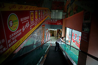 A Trust-Mart supermarket employee rests on an escalator between floors of the supermarket in Nanjing, China.
