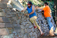 NWA Democrat-Gazette/DAVID GOTTSCHALK  Drew Harriman (left), of Fayetteville, and Brian Richardson, of Hogeye, both local masons, use Ozark native stone Thursday, September 10, 2015 to build  a traditional dry stack retaining wall at a private residence in Fayetteville. The wall is replacing a concrete wall that collapsed earlier in the year because of weather. The stone will match the intended architectural materials of the house.