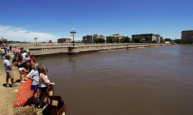 People gather to look at high water in the Des Moines River downtown Friday, June 13, 2008.