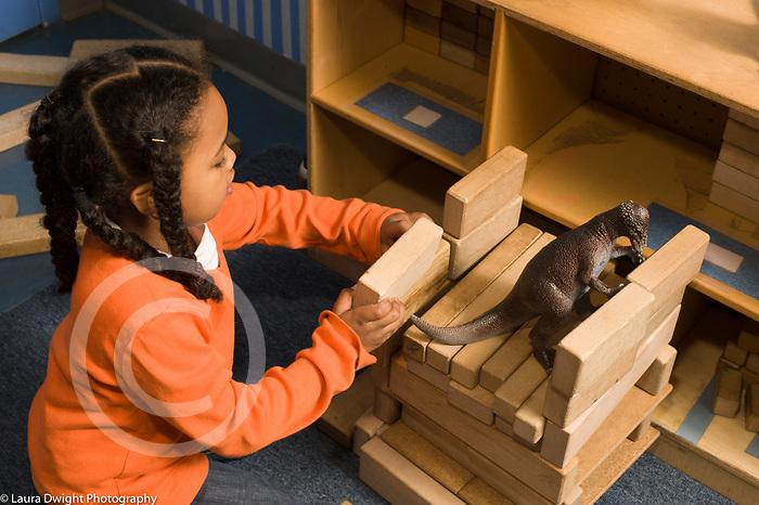Educaton preschool 4-5 year olds block area girl working on construction made of wooden blocks plastic dinosaur inside horizontal