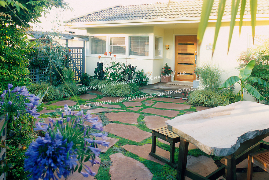 Tropical plantings surround a stone patio in this private garden.