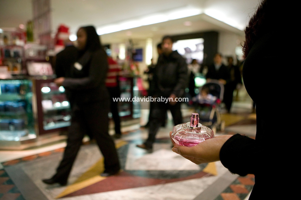 6 December 2006 - New York City, NY - A sales assistant hands out perfume tets to shoppers inside the Macy's department store in New York City, USA, 6 December 2006.