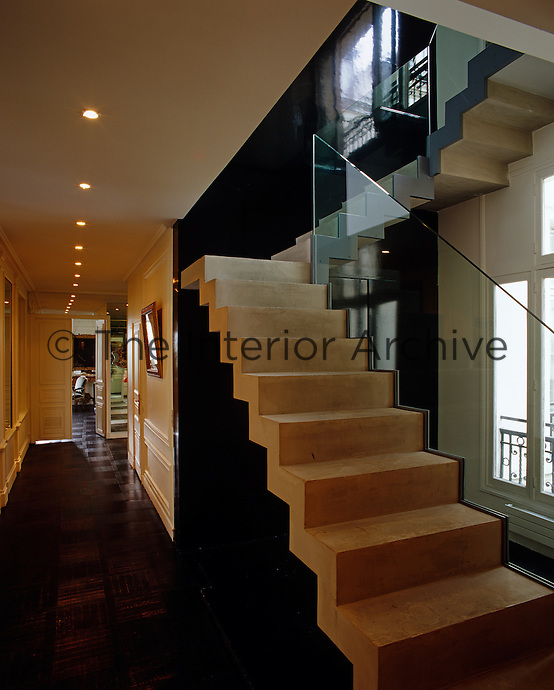 Spotlights line the hallway leading to the living room with a modern, open concrete staircase in the foreground