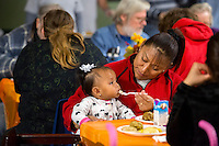 NWA Democrat-Gazette/JASON IVESTER <br /> Dalia Flores feeds her daughter Jennifer Flores, 10 months, both of Springdale, on Tuesday, Nov. 24, 2015, during the annual Thanksgiving dinner at the Samaritan Community Center in Rogers. The center also handed out Blessing Bags filled with Thanksgiving meals and turkeys to visitors. Over 1000 were expected to be served dinner at the Springdale and Rogers centers during the day.
