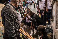 Mourners break apart the coffin as friends and family attend the funeral of Carlos, 26, who died from a fever, in the Grand Cemetery on November 11, 2017 in Port-au-Prince, Haiti. Family members often break apart the coffin to prevent people plundering the costly coffin and trimmings. <br /> Photo Daniel Berehulak for The New York Times