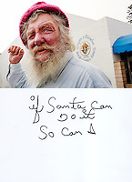 "This is a scan of a print that was given to the subject, Mike Vance, so that he could write his thoughts. He tersely described his feelings by saying:..""if Santa Can Do it So can I.""..Ventura, California, July 20, 2010 - A portrait Mike Vance shows how he has weathered 44 years of living on the streets. He says his red cap and beard lead many to call him Santa Claus. Mr. Vance has been homeless roughly since 1966, when he says he was crushed by a tree that left him unable to hold a steady job. He survives from small SSI checks and the kindness of the local Knights of Columbus Hall that allows him to sleep on their steps and occasionally feeds him. Mr. Vance likes to read and is often seen on these benches and in the neighboring park reading magazines and books people leave behind. Because of the public rest rooms in Mission Park as well as its proximity to the River it is a popular spot for the homeless in Ventura. ."