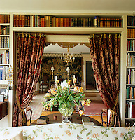 A pair of heavy damask curtains can be drawn to separate the library from the hall