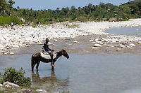 April 9th, 2011_HAITI_ A man cools his horse in a river near the road which links Port Solut to Park Makaya, which is south west of the Haitian capital city of Port au Prince. Park Makaya is in an extremely remote area of Haiti and is known to be a biodiversity hotspot.  Photographer: Daniel J. Groshong/The Hummingfish Foundation