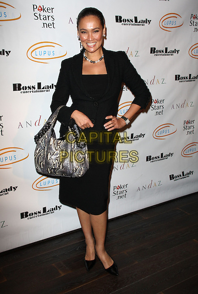 "TIA CARRERE. Lupus LA Raises Awareness with ""Get Lucky for Lupus"" held At Andaz Hotel, West Hollywood, California, USA..February 25th, 2010.full length jacket dress hand on hip snakeskin bag purse black white pearl necklace .CAP/ADM/KB.©Kevan Brooks/AdMedia/Capital Pictures."