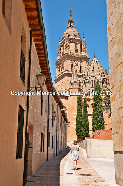 A woman in a white and black polkadot dress walks down a sunny street toward the Catedral Nueva