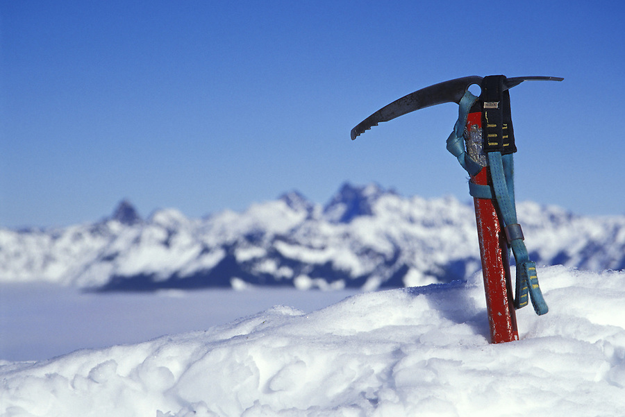 Ice axe in snow in mountains