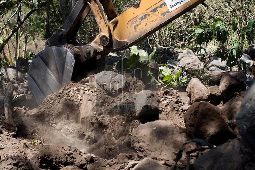 A worker removes stones from an area Panabaj, Guatemala on Saturday, March 17, 2007 during a search for missing bodies remaining buried from a mudslide spawned by rains associated with Hurricane Stan in October 2005. Initially, up to 500 Tzujutil Maya villagers were believed to have been killed by the mudslide, which essentially  wiped away the town. Forensic anthropologists from the Fundación de Antropología Forense de Guatemala have been working to unearth the bodies of the missing and have recovered more than 100. They have also found the number of missing to be lower than originally thought, after many people were located in shelters or living in other towns after the disaster.
