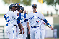 AFL West left fielder Cavan Biggio (26), of the Surprise Saguaros and Toronto Blue Jays organization, first bumps with teammates, including Khalil Lee (15), during player introductions before the Arizona Fall League Fall Stars game at Surprise Stadium on November 3, 2018 in Surprise, Arizona. The AFL West defeated the AFL East 7-6 . (Zachary Lucy/Four Seam Images)