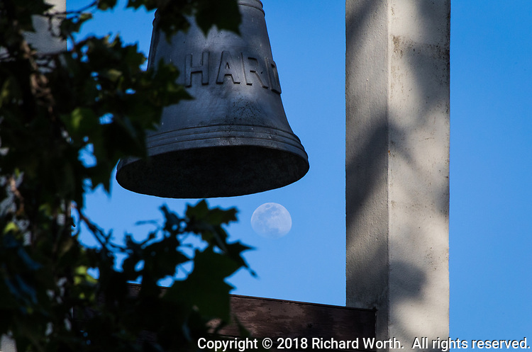 The waxing gibbous moon floats just below one of two bells in a bell tower outside the community center at San Felipe Community Park, Hayward, California.