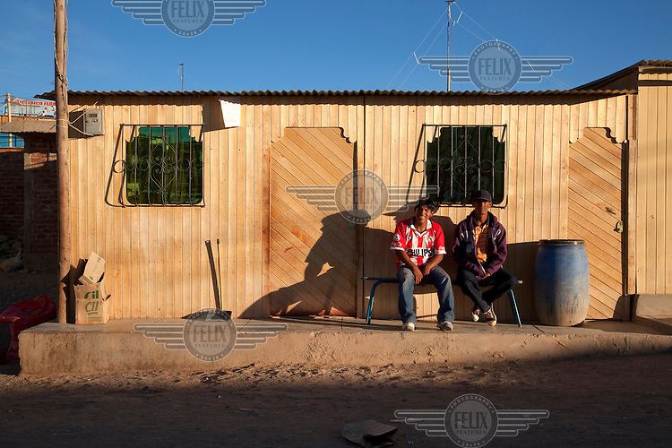 People sit outside their house in the village of Santa Filomena in the department of Ayacucho.