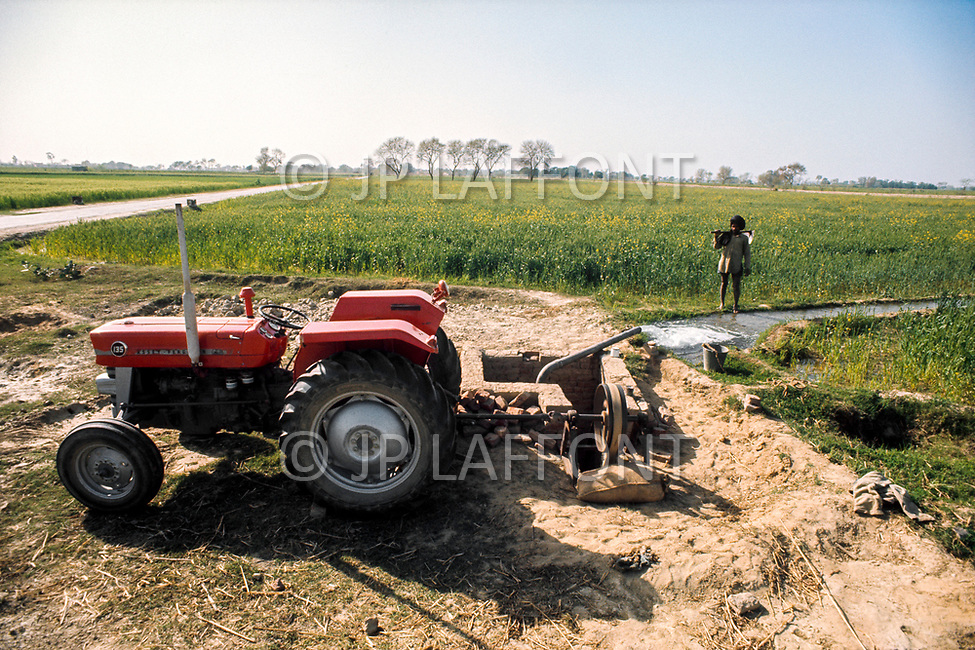 1970, Punjab, India --- A tractor is used to dig an irrigation channel from the Bhakra dam in the Punjab. --- Image by © JP Laffont