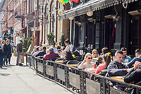 Busy al fresco dining at sidewalk cafes on Sixth Avenue in the New York neighborhood of the Greenwich Village on Saturday, March 22, 2014. (© Richard B. Levine)