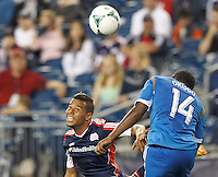 New England Revolution substitute forward Charlie Davies (99) and Philadelphia Union midfielder Amobi Okugo (14) battle for head ball.  In a Major League Soccer (MLS) match, the New England Revolution (dark blue) defeated Philadelphia Union (light blue), 5-1, at Gillette Stadium on August 25, 2013.