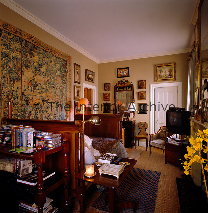 A large tapestry hangs above the bed in this bedroom which is furnished with a selection of antique pieces