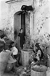 Oaxaca,  Mexican Indian women sit below a  hand crafted Bull firework above the doorway.1973.