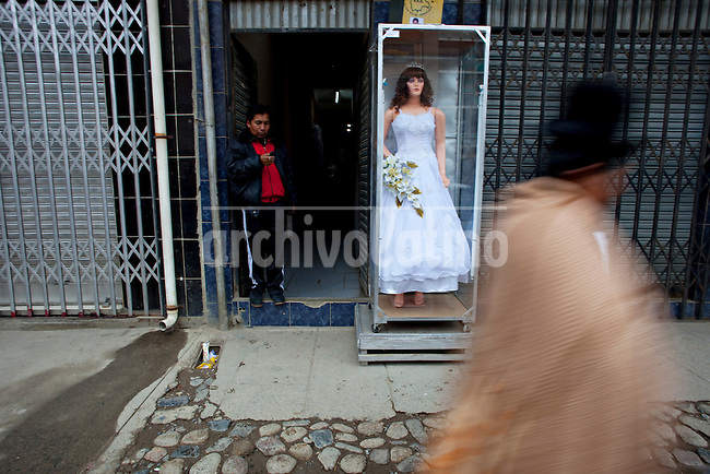 .An Ayamara woman walks pass by a wedding dresses store in El Alto.Just 25 years ago it was a small group of houses around La Paz  airport, at an altitude of 12,000 feet. Now El Alto city  has  nearly one million people, surpassing even the capital of Bolivia, and it is the city of Latin America that grew faster .<br /> It is also a paradigmatic city of the tubles and traumas of the country. There got refugee thousands of miners that lost  their jobs in 90 ´s after the privatization and closure of many mines. The peasants expelled by the lack of land or low prices for their production. Also many who did not want to live in regions where coca  growers and the Army  faced with violence.<br /> In short, anyone who did not have anything at all and was looking for a place to survive ended up in El Alto.<br /> Today is an amazing city. Not only for its size. Also by showing how its inhabitants,the poorest of the poor in one of the poorest countries in Latin America, managed to get into society, to get some economic development, to replace their firs  cardboard houses with  new ones made with bricks ,  to trace its streets,  to raise their clubs, churches and schools for their children.