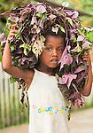 Girl carries home a Medusa-like wig of veggies, Lobo Village, Papua