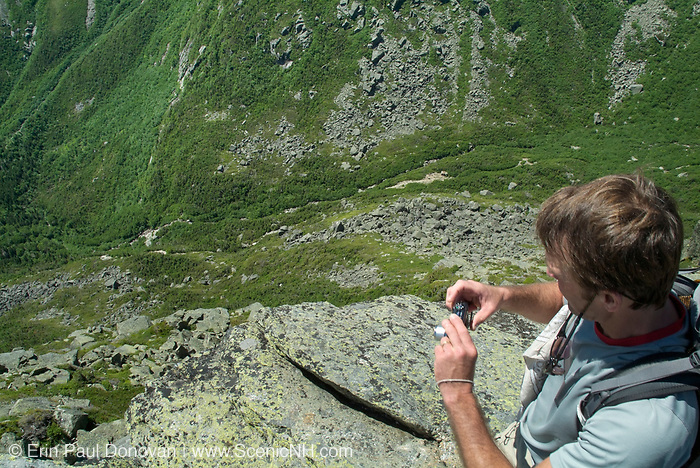 A hiker photographs Tuckerman Ravine during the summer months from along the Lion Head Trail in Sargent's Purchase in the New Hampshire White Mountains; this area is part of the Presidential Range.