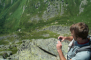 A hiker photographs Tuckerman Ravine from Lions Head Trail during the summer months in the White Mountains, New Hampshire USA. Tuckerman Ravine Trail can be seen down in the ravine. Tuckerman Ravine is located on the eastern slopes of Mount Washington.