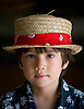 A boy wears a handmade lauhala hat at the Kimura Lauhala Shop in Kona, Hawaii. Photo by Kevin J. Miyazaki/Redux