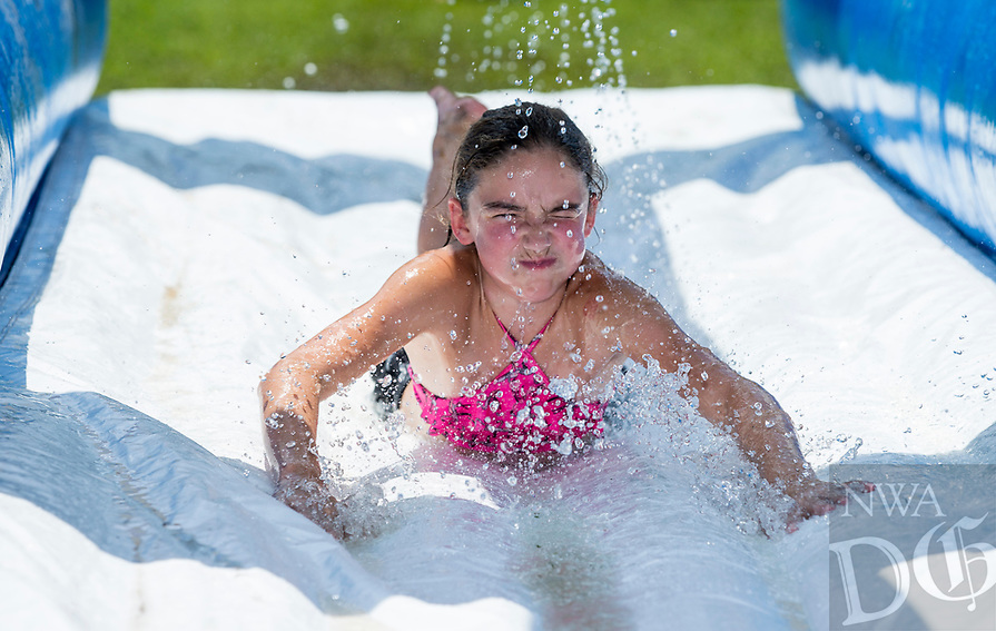 NWA Democrat-Gazette/BEN GOFF @NWABENGOFF<br /> Sadie Hayes, 10, of Bentonville dives through a water slide Tuesday, Aug. 6, 2019, during the Summer Day Camp at the Rogers Activity Center. This week's camp is the center's final session of the summer season.