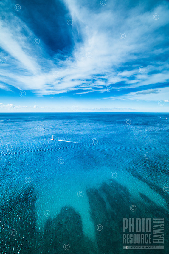 An aerial view of boats cruising off the coast of O'ahu's Waikiki on a peaceful day.
