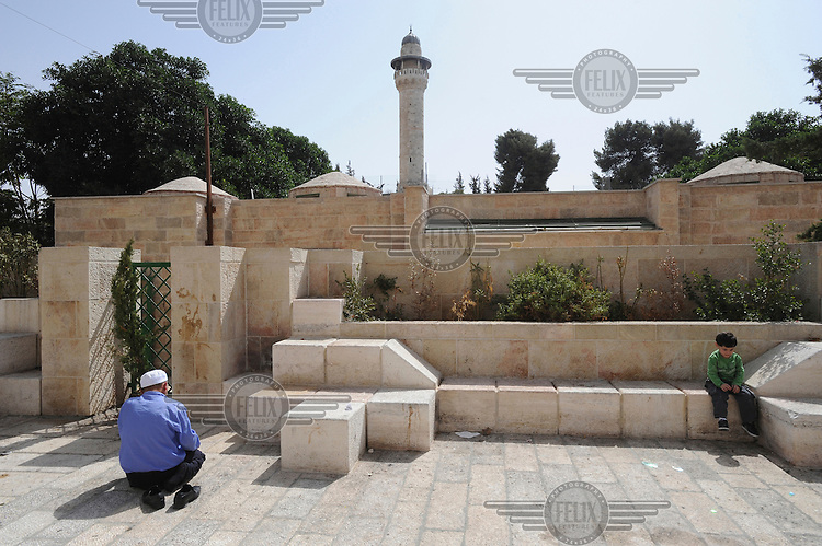 A Muslim man prays outside Al-Aqsa mosque compound in Jerusalem's old city. Following violent clashes between Muslims and Israeli police inside the compound, police denied entry to Muslims younger than 50 into Al-Aqsa.
