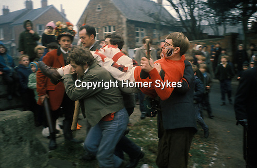 Haxey Hood Game. Haxey Lincolnshire 1970s. Catching the Fool and taking him to the Mounting Block where he will be 'smoked'. Peter Bee as The Fool.1971 or 1972. The Lord is Stan Boor who's is holding the Sway Hood.