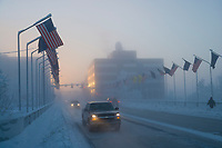 Vehicle traffic in ice fog on Illinois street in downtown Fairbanks during winter temperatures of minus 40 degrees