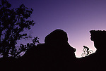 A photo of a man riding his mountain bike between two large boulders with a purple sky background near Smith Rock, OR.
