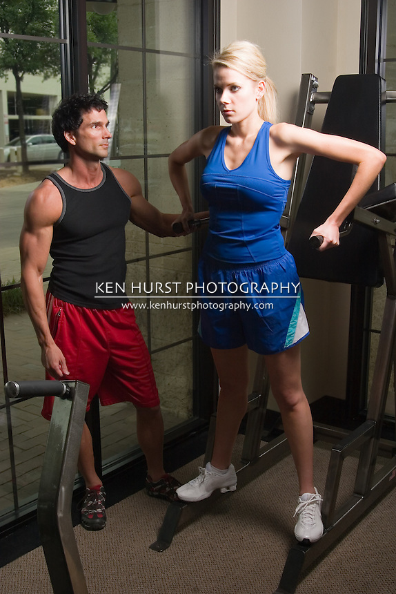 Man and woman exercising together at a fitness center on exercise equipment.  Man could be a personal fitness trainer.