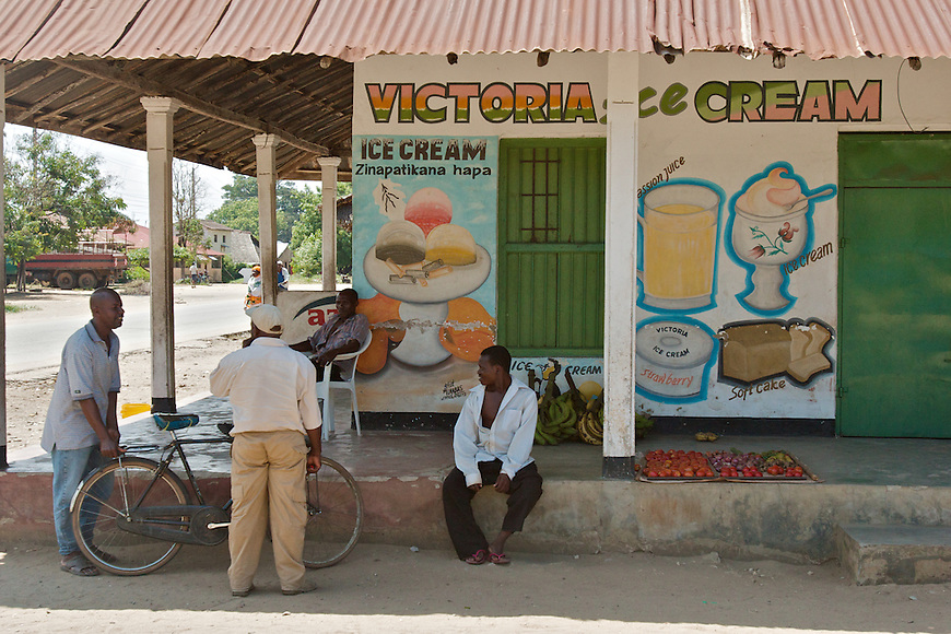 Tanga residents gather under the shade. Entrepreneurs operate a fruit stand and bike repair shop off the porch of a closed ice cream store.
