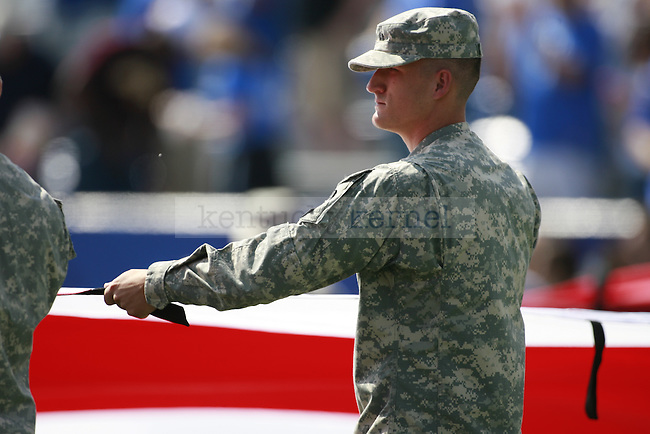 A soldier holds onto a giant American Flag before the first half of UK's first home game against Central Michigan, Saturday, Sept. 10, 2011 in Lexington, Ky.  Photo by Brandon Goodwin | Staff