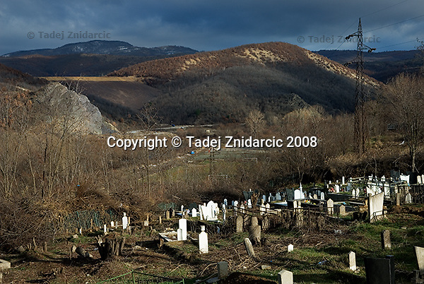Muslim and Roma cemetery in northern Mitrovica. Across the valley is the artifical dam built from tailings, the toxic remnants from processing of lead and zinc ores at the nearby Trepca mining complex. The dust from toxic tailings is blown by wind down to the city and particularly to the two IDP camps which are located at the bottom of the Ibar river valley. The crest of the dam has been rehabilitated, though after rain puddles still turn red.