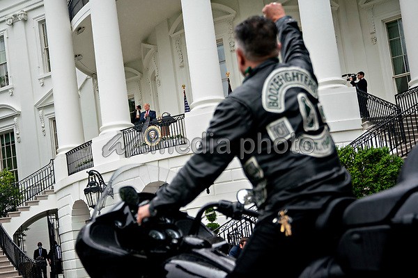 United States President Donald J. Trump, center left, watches as actor Robbert Patrick ride a motorcycle past the White House during a Rolling to Remember ceremony honoring the nation's veterans and prisoners of war/missing in action (POW/MIA) in Washington, D.C., U.S., on Friday, May 22, 2020. Trump didn't wear a face mask during most of his tour of Ford Motor Co.'s ventilator facility Thursday, defying the automaker's policies and seeking to portray an image of normalcy even as American coronavirus deaths approach 100,000. <br /> Credit: Andrew Harrer / Pool via CNP/AdMedia