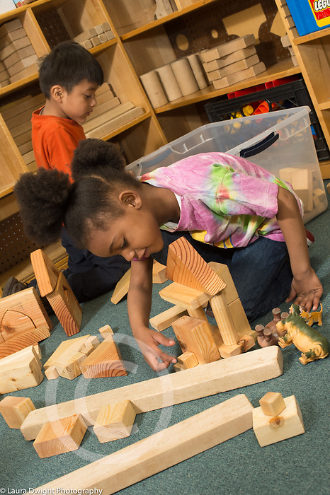 Education preschool 3-4 year olds girl building with wooden blocks in classroom, boy building in background. Looking over construction to place small block