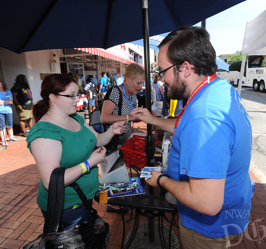 NWA Democrat-Gazette/ANDY SHUPE<br /> Rebecca Yzaguirre (left), a Sam's Club associated from Indianapolis, exchanges Sam's Club-themed pins with Nicholas Graves, archivist for the Walmart Museum, Wednesday, June 3, 2015, on the Bentonville square. Yzaguirre and other associates is in the area for the annual shareholders meeting.