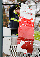 NWA Democrat-Gazette/DAVID GOTTSCHALK  Kevin Henson, signal technician with the city of Fayetteville Transportation Division, hangs a seasonal banner Monday, November 16, 2015 on School Avenue in Fayetteville.  The Lights of the Ozarks will begin Friday night and run through December 31, 2015.