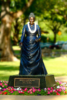 Lei-draped statue of Queen Kapiolani against a  background of muted green trees near the Waikiki bandstand in Kapiolani Park, Waikiki.