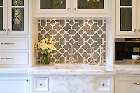 This custom kitchen features a Chatham 1 mosaic backsplash shown in Bardiglio and Calacatta Tia from the Silk Road collection by New Ravenna.<br />