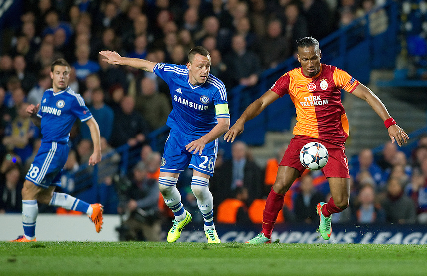 Galatasaray's Didier Drogba vies for possession with Chelsea's John Terry<br /> <br /> Photo by Ashley Western/CameraSport<br /> <br /> Football - UEFA Champions League First Knockout Round 2nd Leg - Chelsea v Galatasaray - Tuesday 18th March 2014 - Stamford Bridge - London<br />  <br /> &copy; CameraSport - 43 Linden Ave. Countesthorpe. Leicester. England. LE8 5PG - Tel: +44 (0) 116 277 4147 - admin@camerasport.com - www.camerasport.com